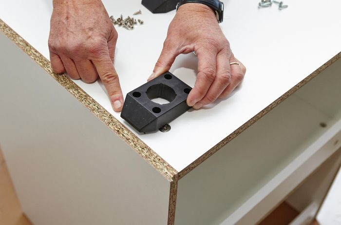 Person attaching base of feet to cupboard
