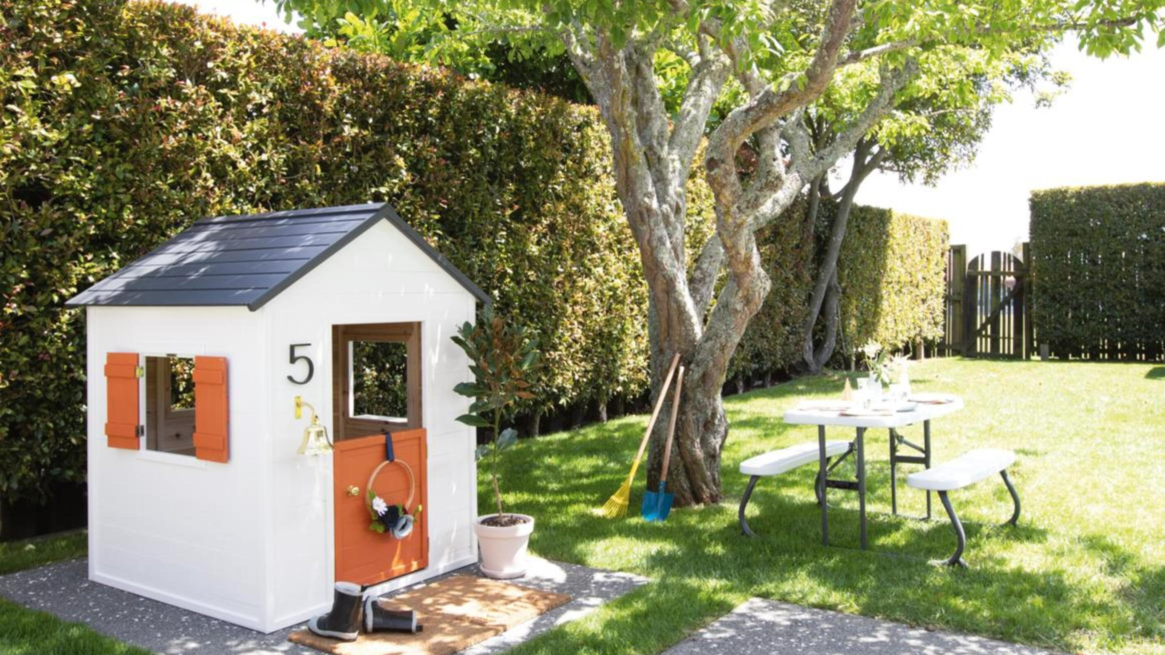 Green garden with tree, pinic table and cubby house.