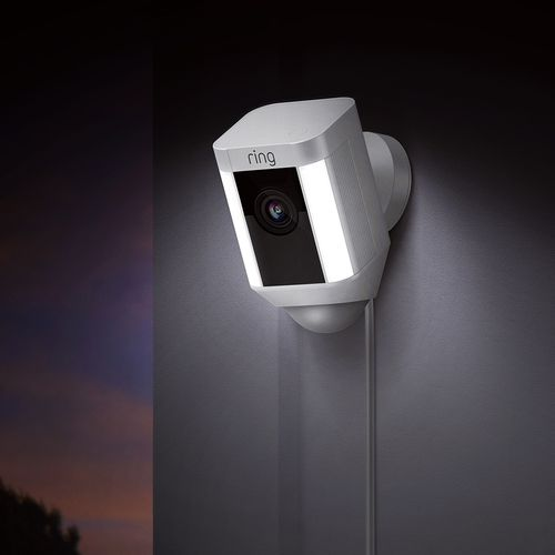 Outdoor security camera attached to wall with built-in lights