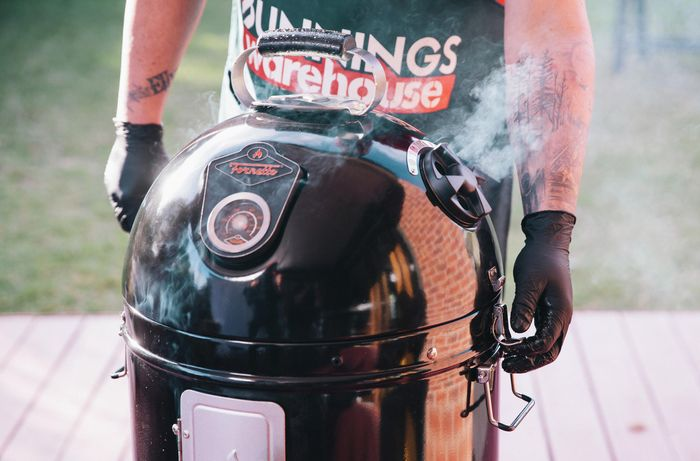 Person standing next to a bullet smoker with smoke coming out