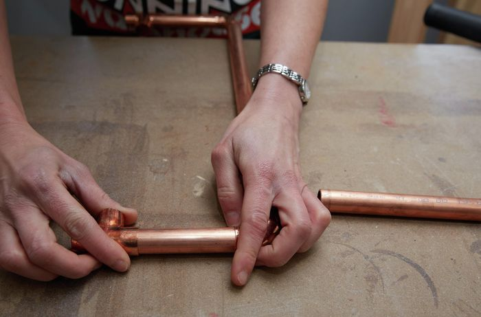 Person connecting copper pipe to copper joining
