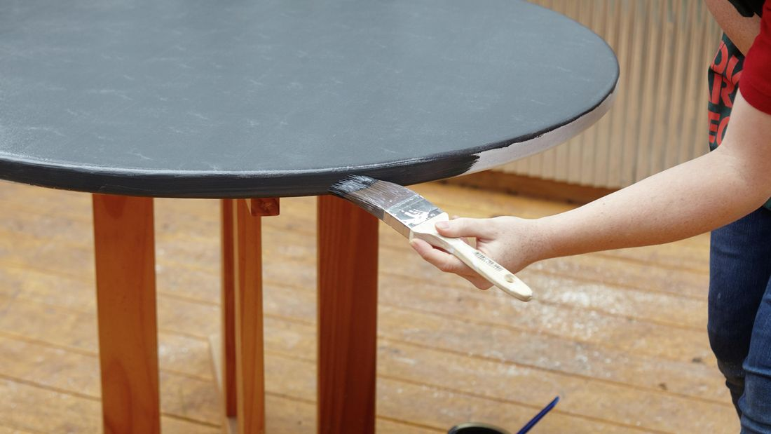 A Bunnings team member painting the edge of a table in Bunnings teal