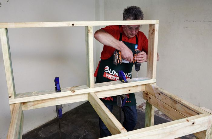 A person drilling a hole in a vertical section of framing