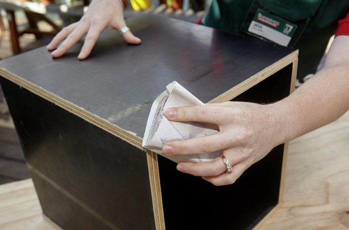 A constructed wooden storage box being sanded down with sandpaper