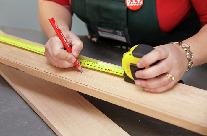 Person using tape measure to mark cuts to be made