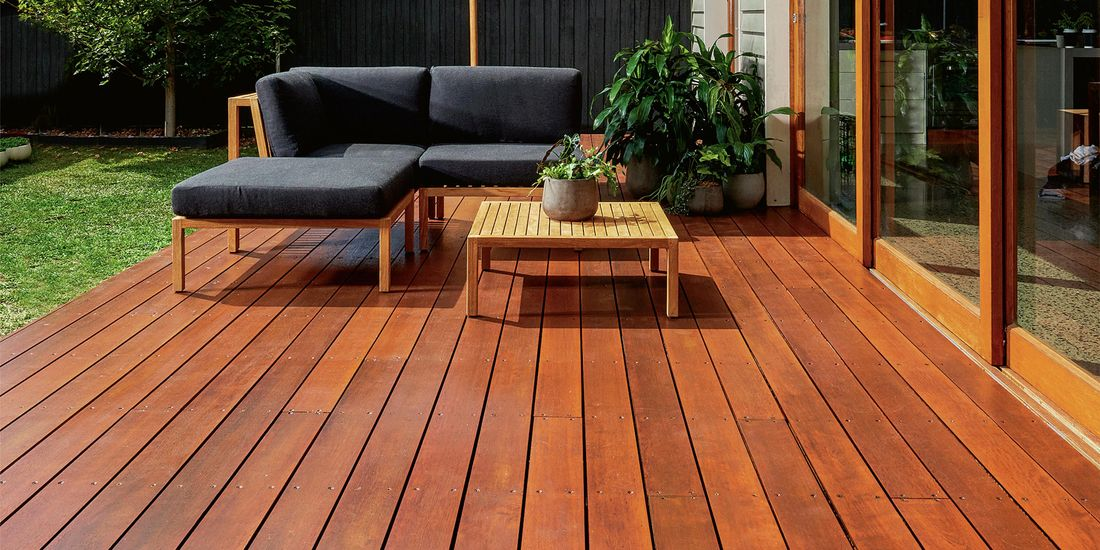 A stained backyard deck complete with timber outdoor coffee table, outdoor sofas and pot plants, with a lawn and tree in the background