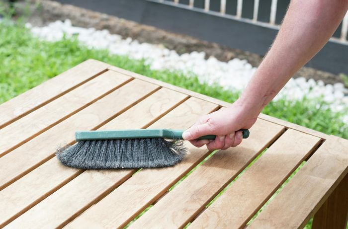 Brush wiping down timber table