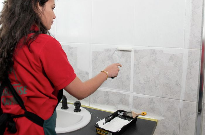 Person painting tiles white with a roller.