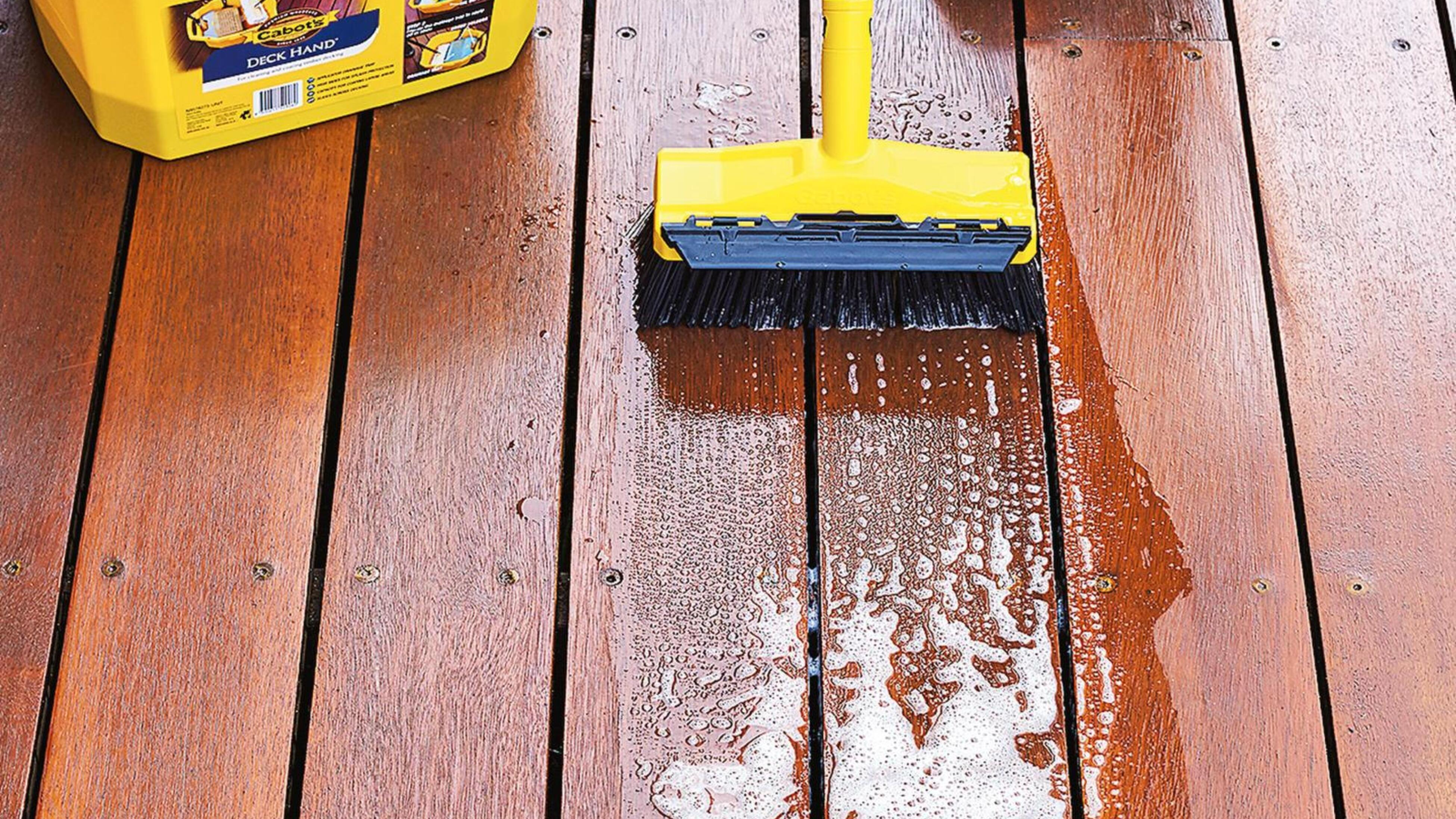 Outdoor deck being scrubbed with Cabot's Deck Hand product.