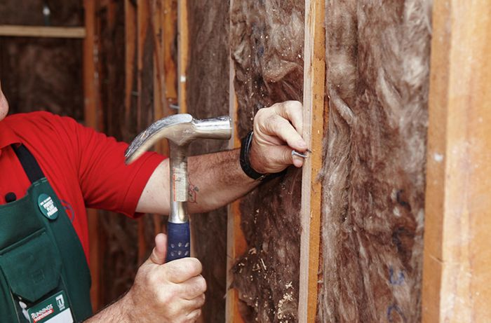 A nail being hammered into a wall beam as part of a ledge for villa board panels