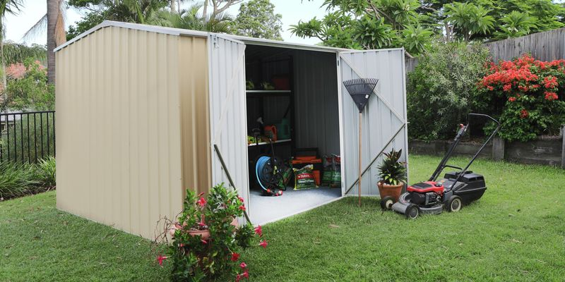 Cream shed and a lawn mower in a garden