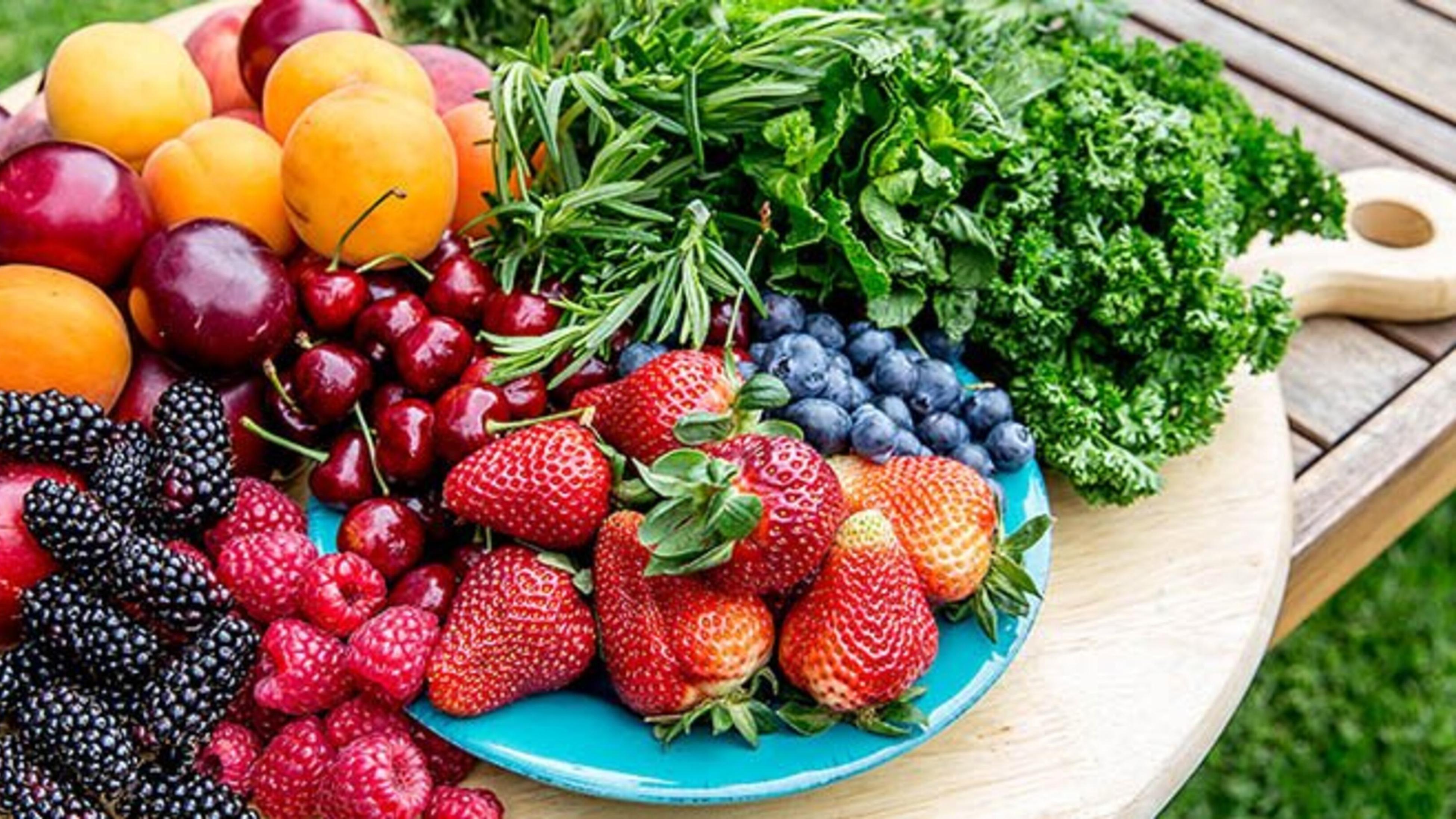Harvested fruit and vegetables including blackberries, raspberries, strawberries, blueberries and cherries.