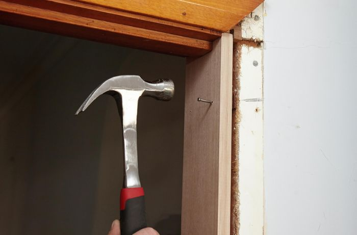 A new door jamb being nailed into place