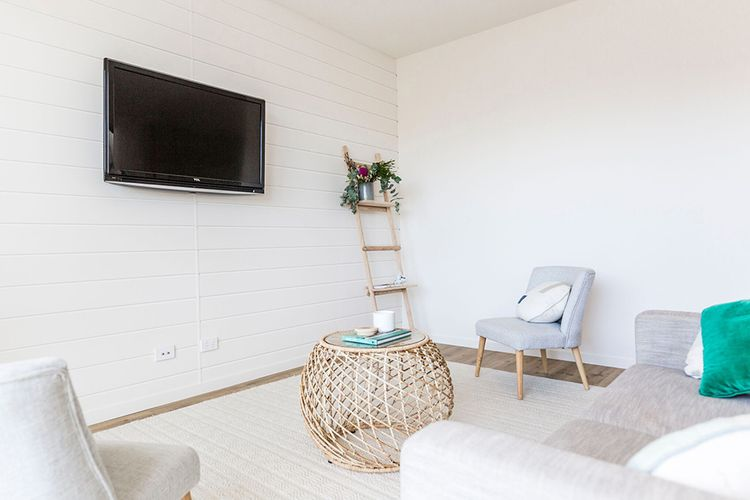 Light lounge area with wicker feature table and wall mounted TV