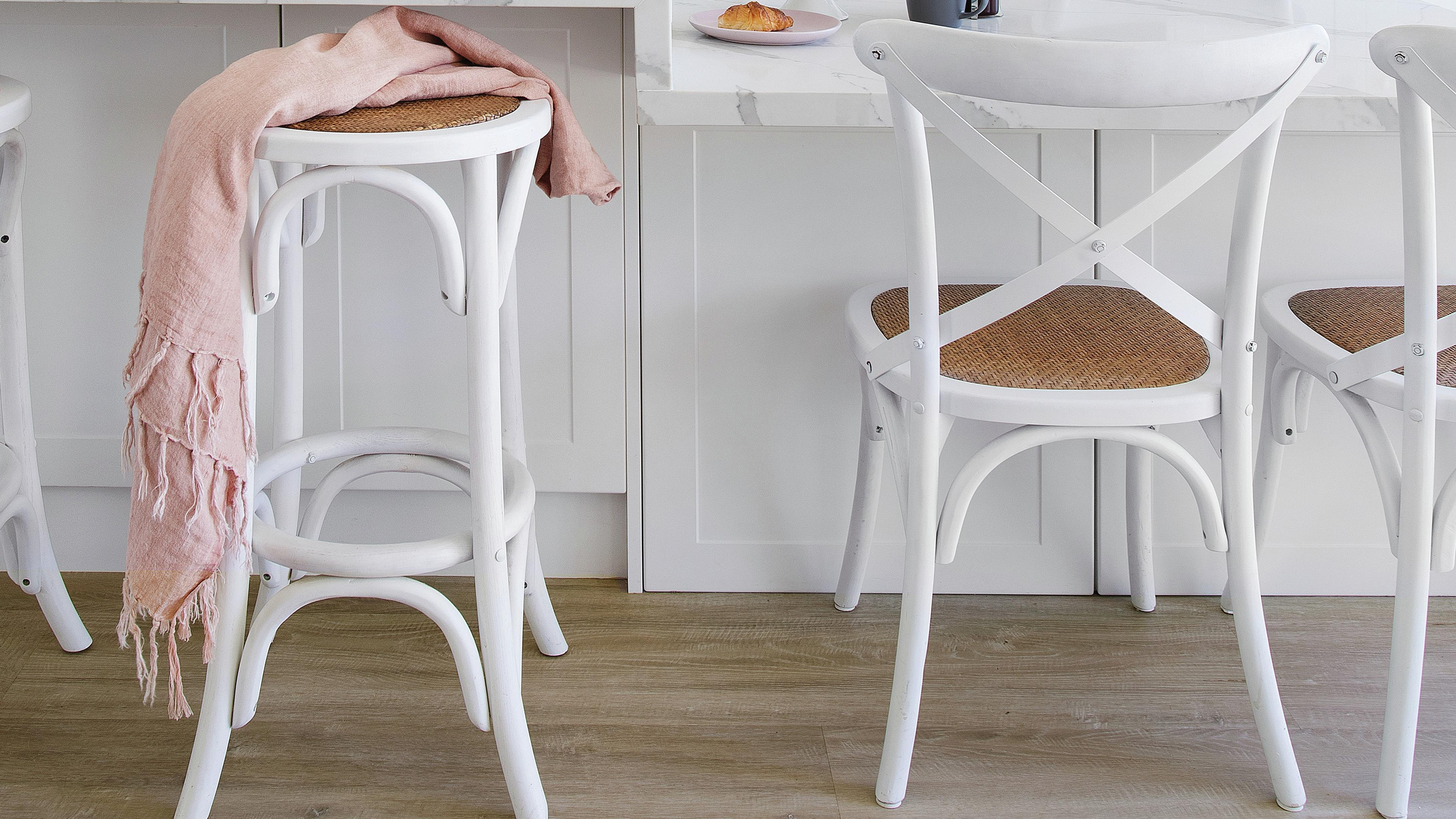 White bar stools and a pale pink scarf draped over a stool.