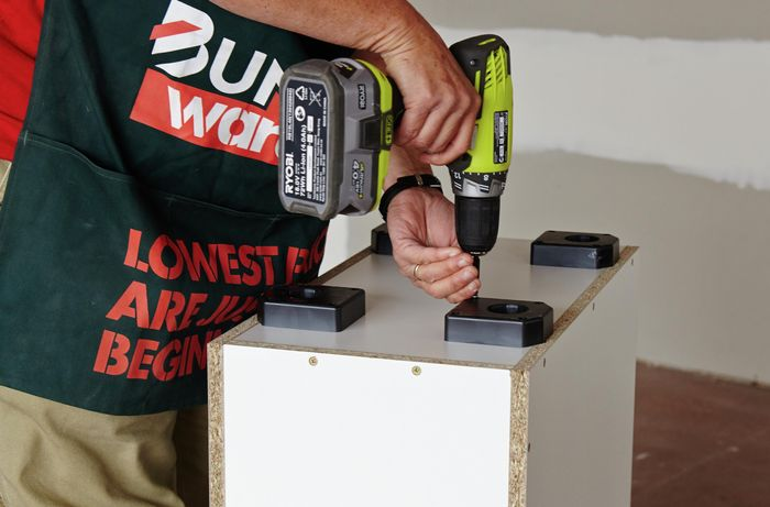 Person attaching plastic feet to cabinet using a drill
