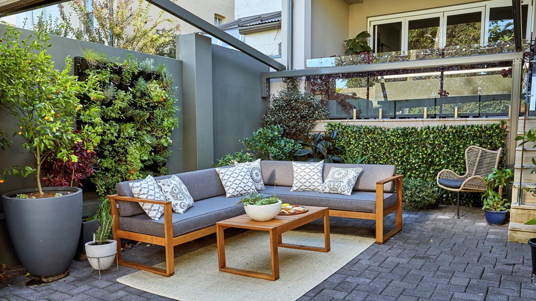 Outdoor entertaining area with outdoor furniture and vertical wall gardens.