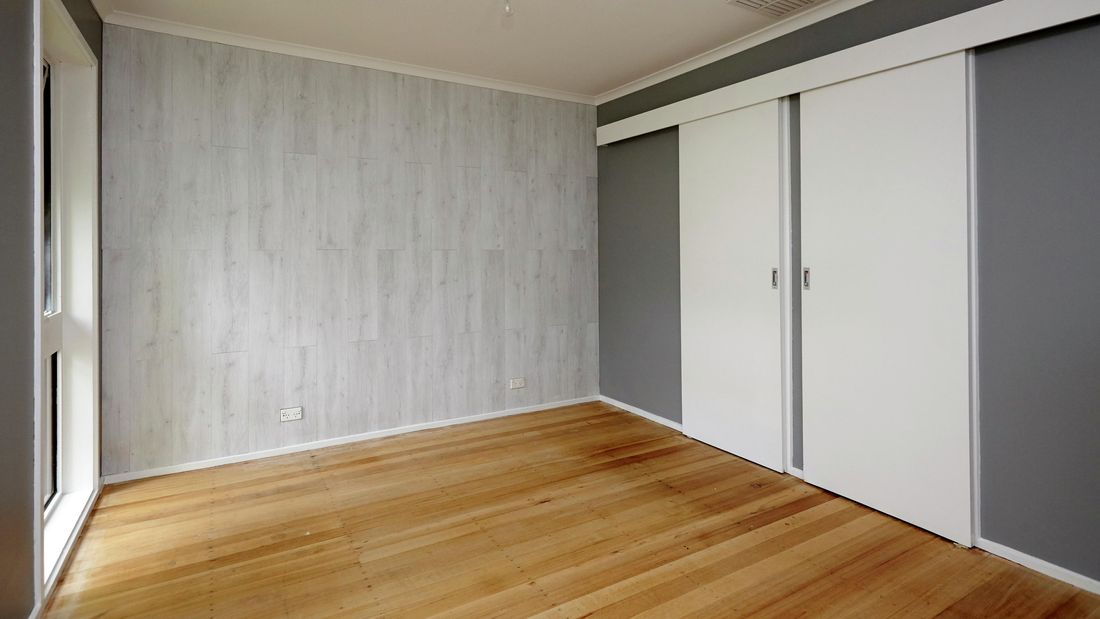 An empty room with a timber floor and a pale timber looking feature wall