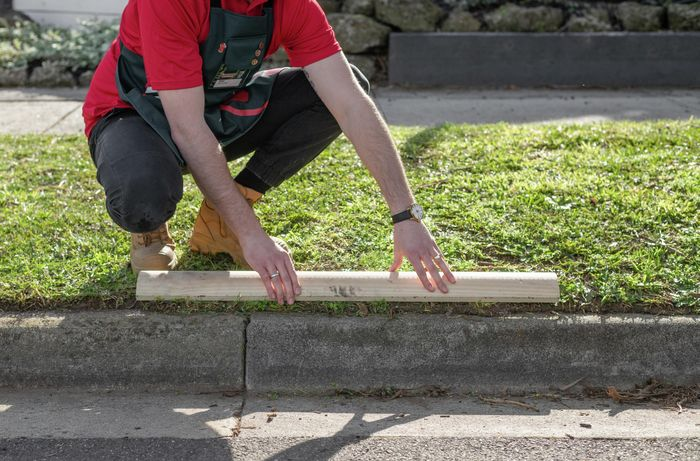 Person using bit of timber to see where edges of lawn should be.