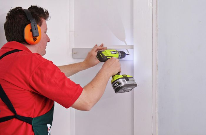Person drilling cleat to wall.