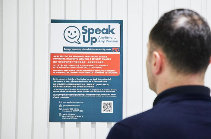 man looking at in store speak up poster