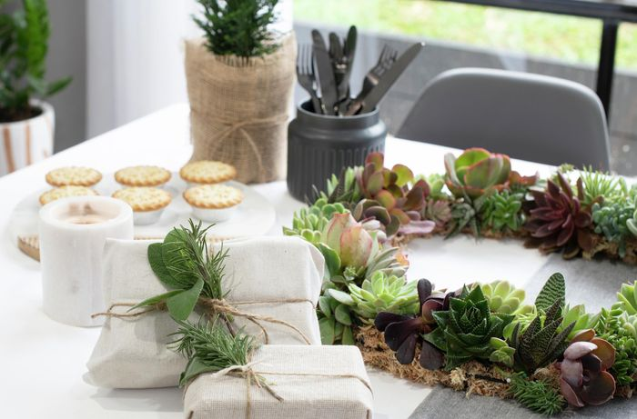 Table with food, presents and succulent wreath on it.