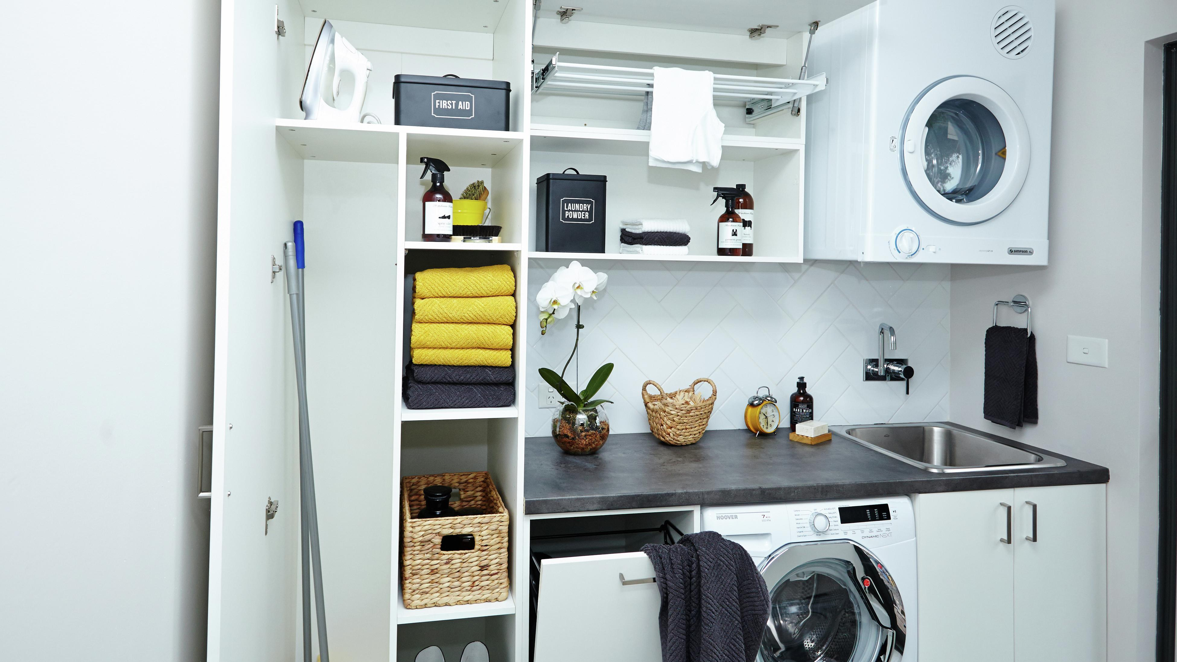 Tidy broom cupboard featuring brooms, towels, a washing machine and dryer.