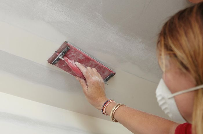 A person wearing a mask sanding a join in a plaster ceiling