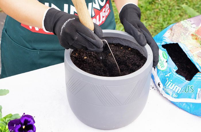 A person making a hole for a plant in a pot of soil