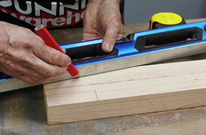 A spirit level and a pencil being used to rule an angled cut marker into a piece of timber