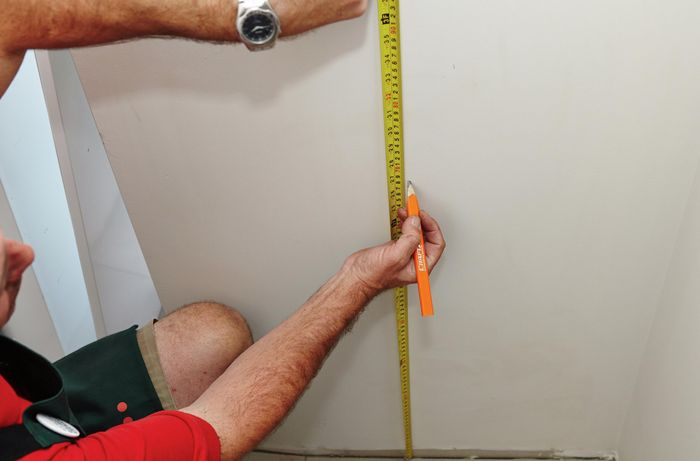 Using a measuring tape and pencil to mark the wall.