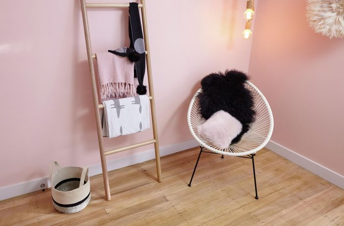 Room with pink wall, wooden ladder, basket and chair.