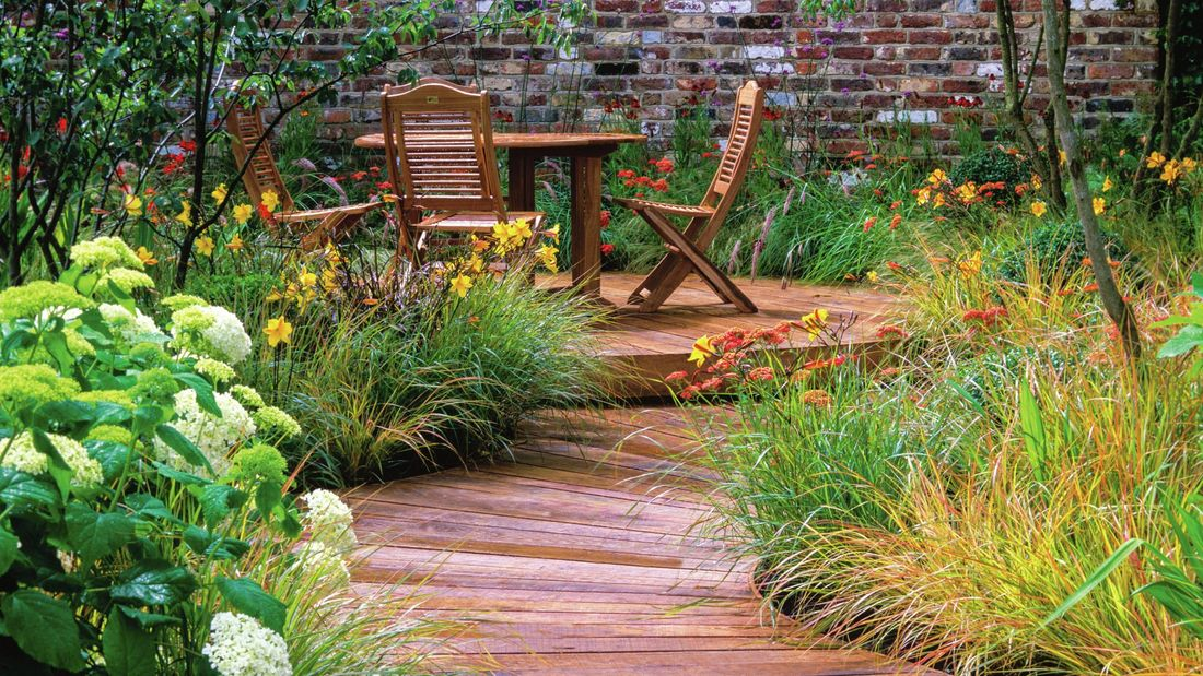 Wooden path with a table and chairs within a garden setting and flowering daffodils.