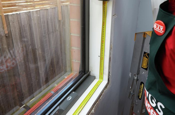 A person measuring the base of a window opening in a room