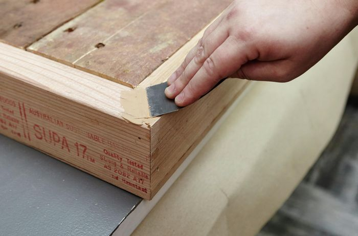 Putty being used to seal the joints in a pallet coffee table