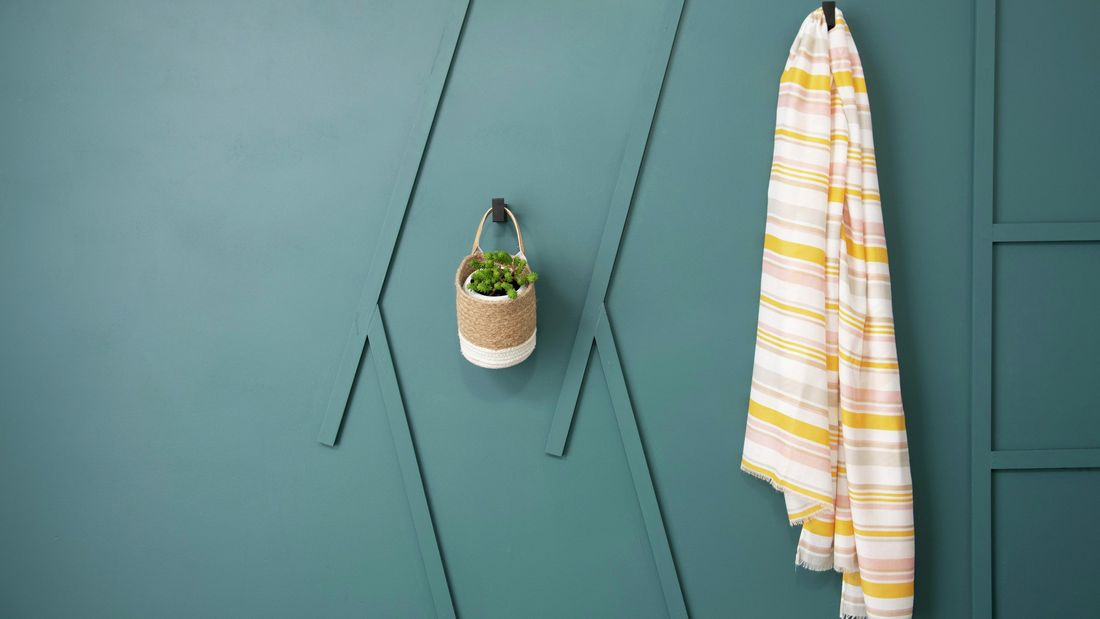 Small pot plant basket and towel hanging off green wall.