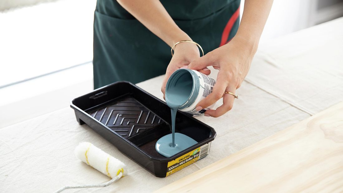 Pouring paint out of a paint pot into a paint tray