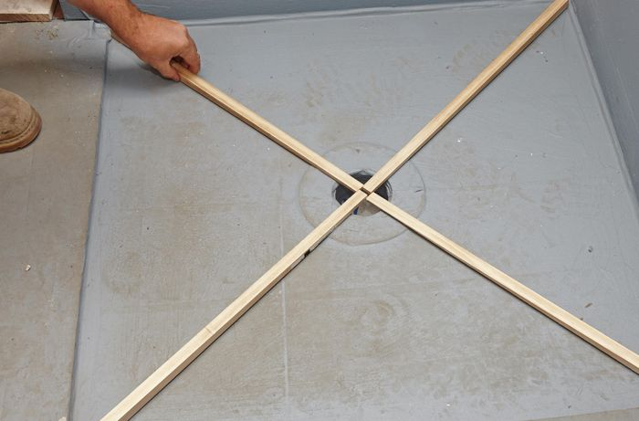 A person placing four wedge-shaped lengths of timber in an X across a shower base