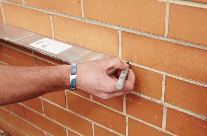 A person marking a brick wall using a metal lintel and marker pen