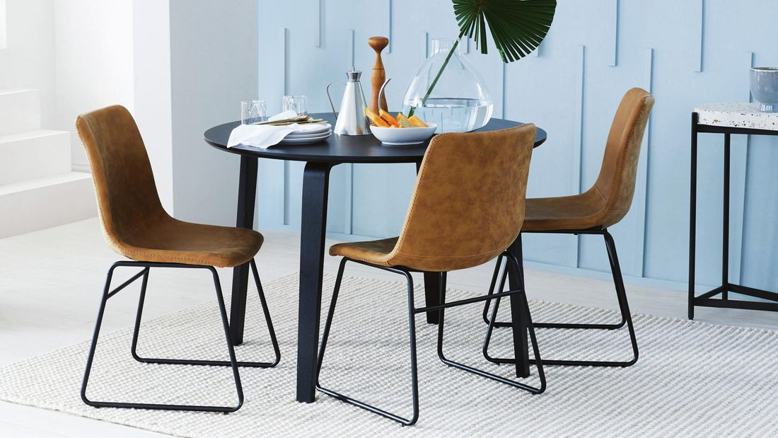 Black circular table surrounded by three brown leather chairs