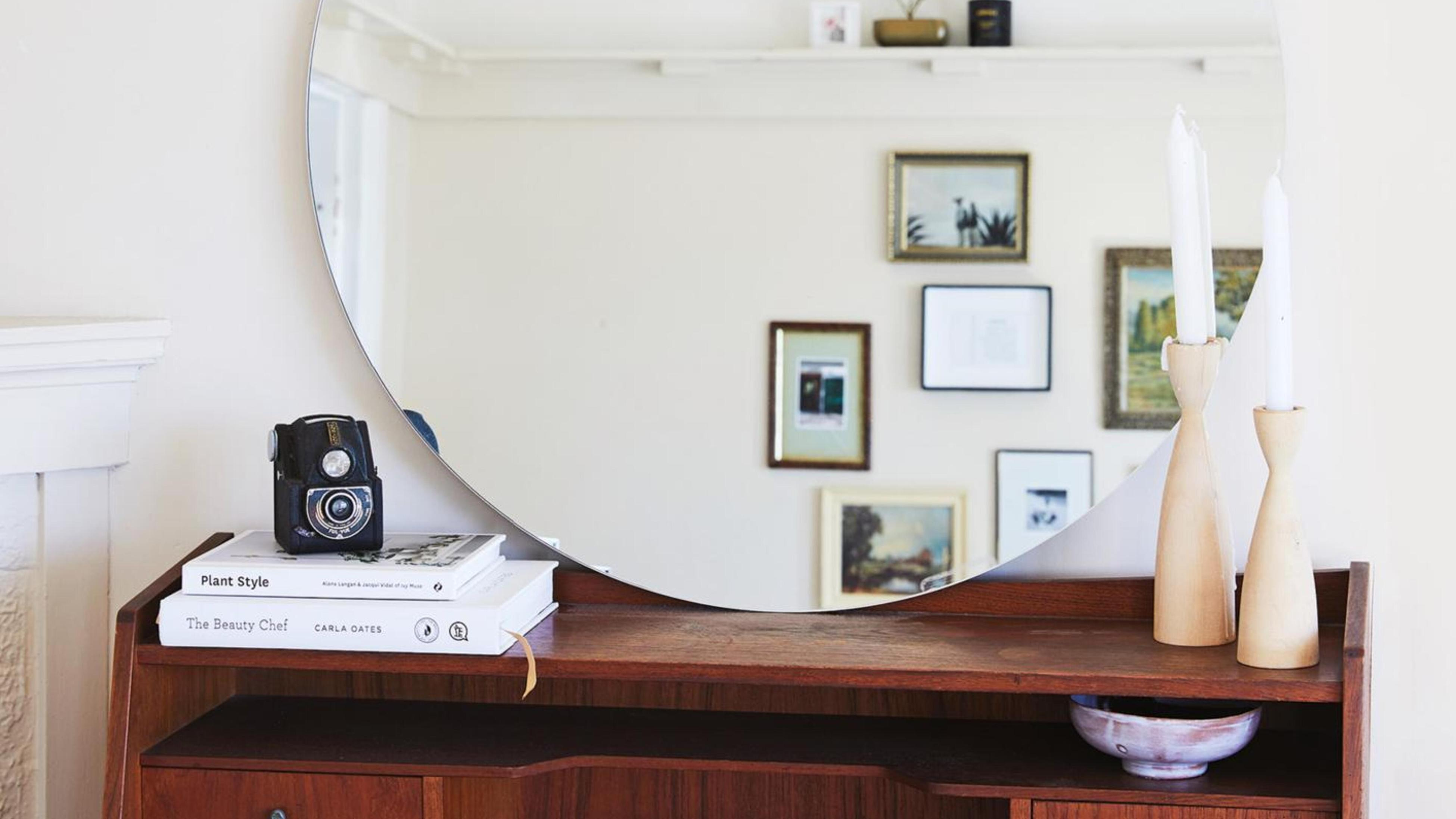 A shelf with a mirror, camera, books and candles on top. In the reflection of the mirror are hanging picture frames.