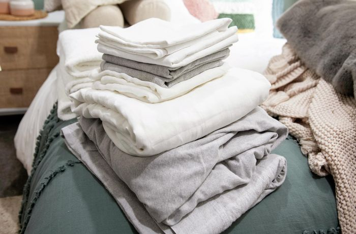 Stack of bed linen sitting on a bed