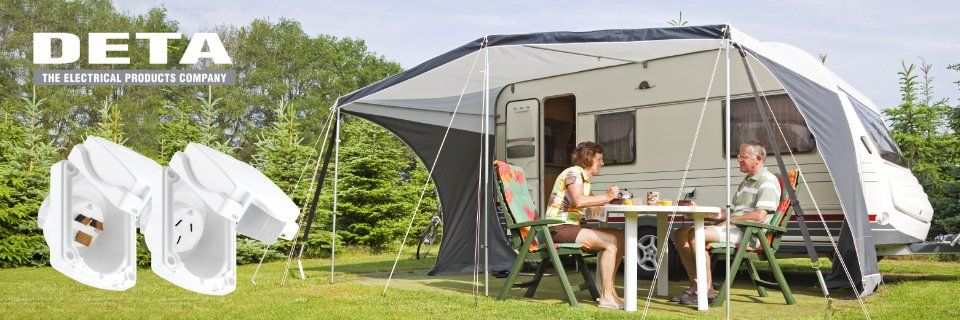Deta- the electrical products company. Caravan with couple sitting under awning.