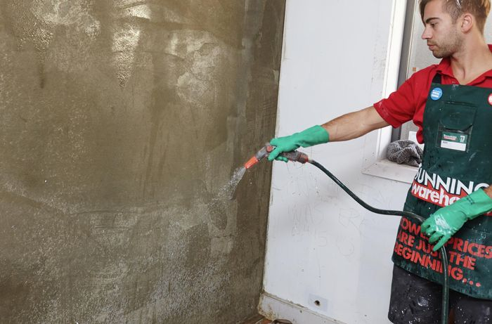 An indoor wall being hosed down before plaster is applied