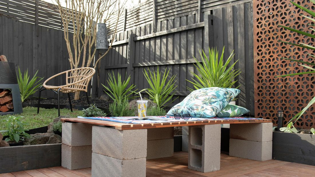 A slatted timber garden seat resting on concrete blocks