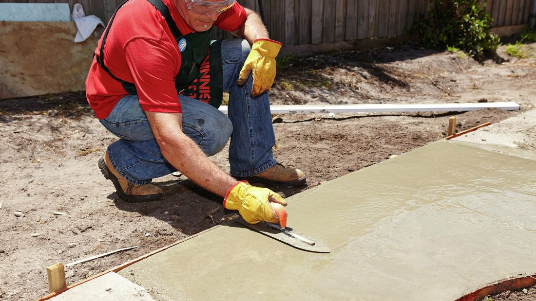 Bunnings team member using a trowel to smooth the wet concrete of an outdoor pathway