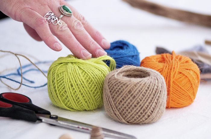 Green, blue, orange and brown rolls of string.