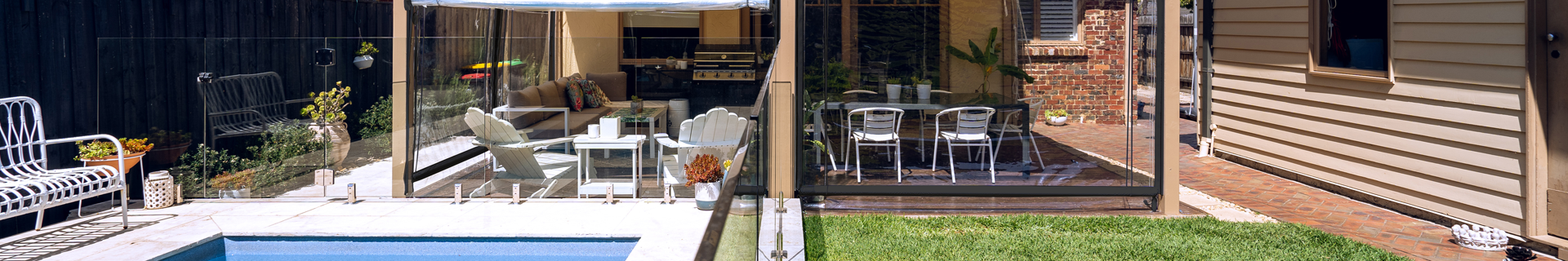 Outdoor entertaining area with clear roller blinds.