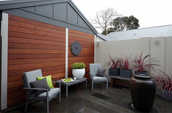 A modest outdoor area with seats, pots and planters