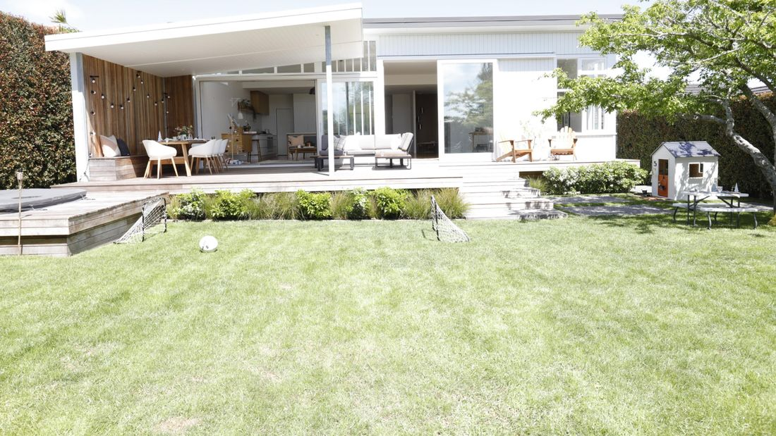A white house with a front lawn and outdoor setting.